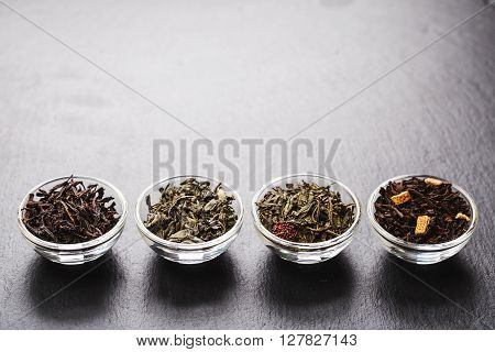 Four bowls with different types of tea: black and green, are standing on black stone textured backgroung. Place for your text.