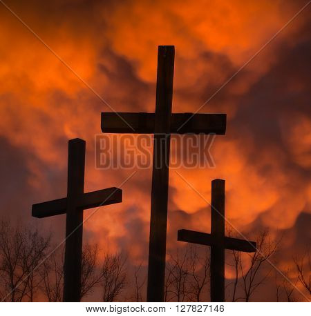 three crucifixes and mammatus clouds on dark night