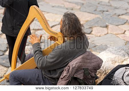PORTOVENERE ITALY - MARCH 25 2016: Street musician playing harp for tourist that are visiting the ancient church of San Pietro in Portovenere or Porto Venere - La Spezia Liguria Italy