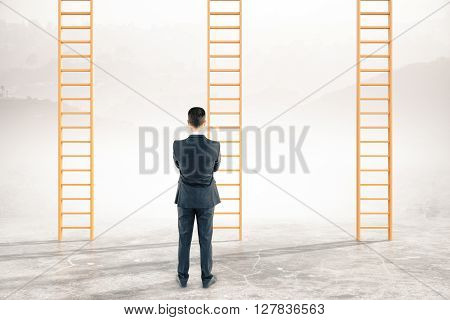 Thoughtful businessman looking at career ladders on abstract landscape background