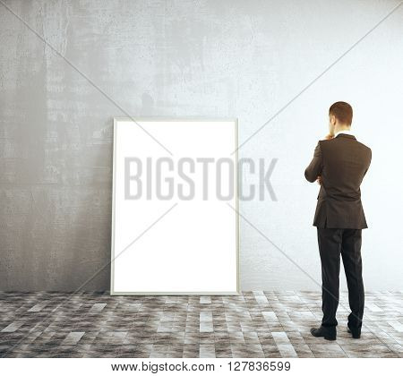 Thoughtful businessman looking at blank picture frame in room with concrete wall and tile floor. Mock up 3D Rendering