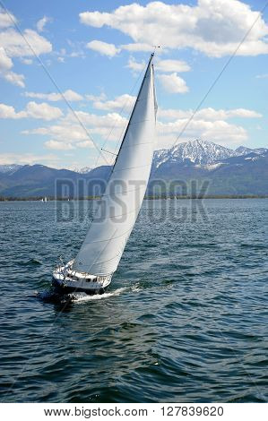 Sailboat with white sail on Lake Chiemsee Bavaria