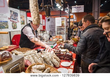 People Buying Meat From Butcher At Covered Market