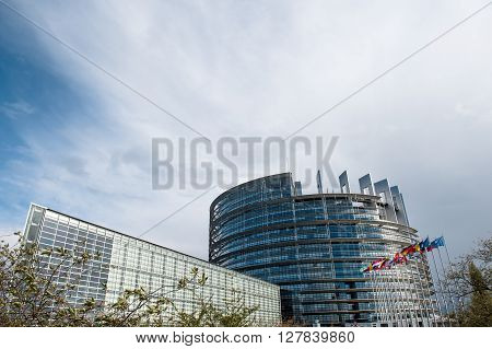 STRASBOURG, FRANCE - MARCH 12, 2016: European Parliament building with all European union flags waving in wind on a spring day in Strasbourg France Alsace