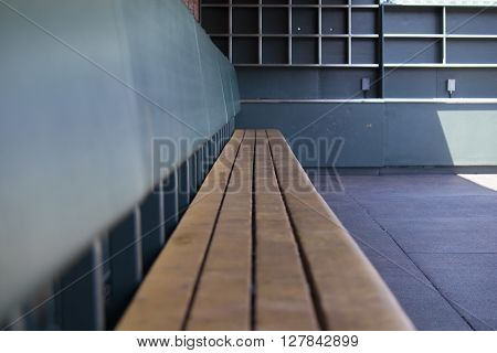 empty bench in a baseball dugout in the shadows