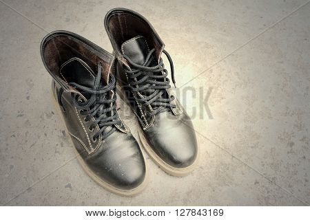 Black leather boots on a cement background.