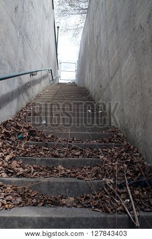 A cement stairway adjacent to the Broadway Street Bridge allows pedestrians to ascend from Jefferson Street to Broadway Street, near downtown Joliet, Illinois.