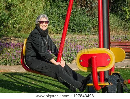 76-year-old woman in sunglasses tries out knee bender machine in her local park. Grey-haired woman in black sport suit is working out at outdoor gym. She enhances flexibility of her waist and legs. Promote health and well-being lifestyle concept.