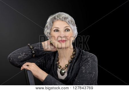 Portrait of senior woman with tiger iron eye beads necklace heart pendant bracelet ring and earrings. Grey haired gorgeous 76-year-old woman sits on chair posing on black background. Horizontal indoors facial picture