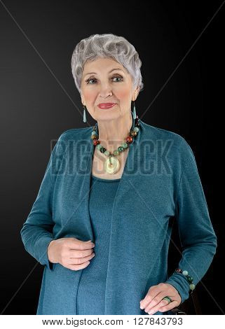 Portrait of spectacular 76-year-old woman wears multi colored semiprecious stone beads necklace with donut pendant and bracelet. Grey haired woman is clothed in old turquoise shrug set. Upper body vertical shot on black background