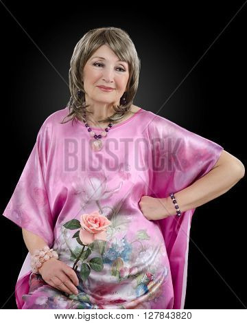 Half-length portrait of pensive 76-year-old woman dresses in pink silk robe and holds pink rose with right hand. In addition she wears blonde wig amethyst rose quartz bead necklace and bracelets. Studio vertical shoot on black background