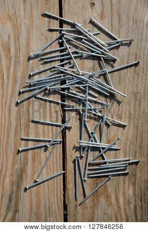 Batch of nails on brown wooden planks