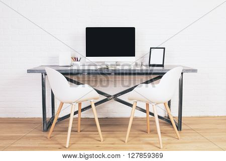 Two white chairs next to designer table with blank computer screen and other items on wooden floor and brick background. Mock up