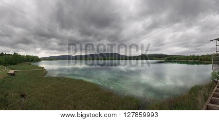 Aerial panorama view of Lake Banyoles. Mirrored clouds on the cristal clear water.