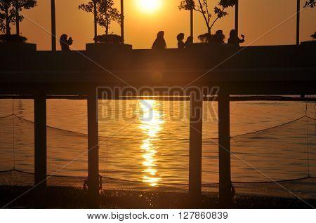 People walk on the bridge during sunset.