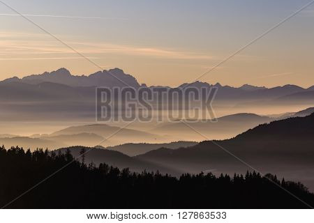 Beautiful landscape with mountains and fog in valleys after sunset.In backgroung Karawanks mountains.Carinthia,Austria.