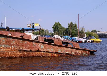 Old abandoned rusty boat in river and new motor boats on summer day