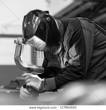Industrial worker with protective mask welding inox elements in steel structures manufacture workshop. Black and white photo.