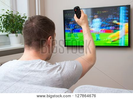 Goal! Man Watching Football Match On Television At Home.