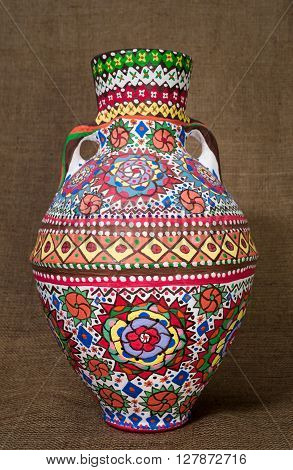 A colorful Egyptian handcrafted artistic ornate pottery jar on a sackcloth background. one of the art works of Ebtessam ElGohary a contemporary Egyptian artist specialized in pottery painting art. Decorations are inspired by the Mandala style.