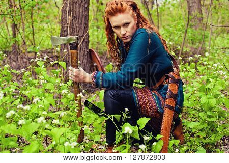 Redhead scandinavian woman posing in a forest with axe