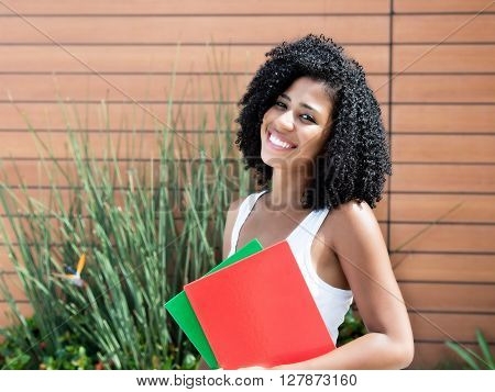 Cute latin female student woman with curly black hair outdoor with plants in the background
