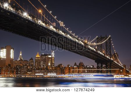 Manhattan Skyline and Manhattan Bridge At Night. Manhattan Bridge is a suspension bridge that crosses the East River in New York City. Long exposure for night image.