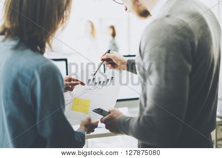Business meeting photo.Photo chart holding man hand.Photo managers crew working with new startup project.Idea presentation, analyze marketing plans, statistics document. Blurred background, horizontal