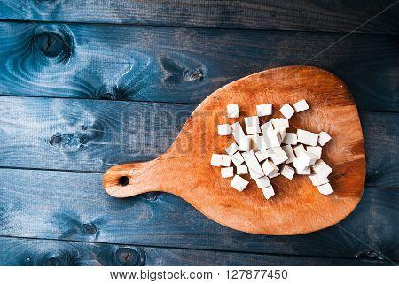 Cubes of raw tofu on shabby cutting board