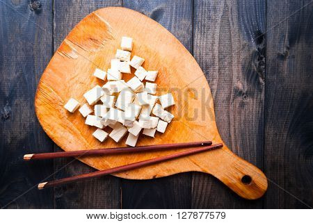 Cubes of raw tofu and two chopsticks on shabby cutting board