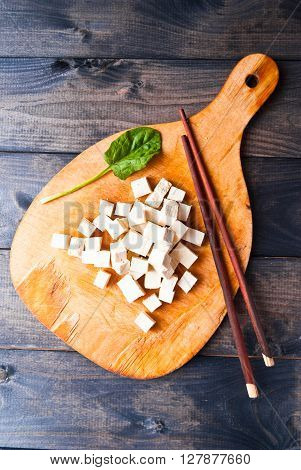 Cubes of raw tofu spinach and chopsticks on shabby cutting board
