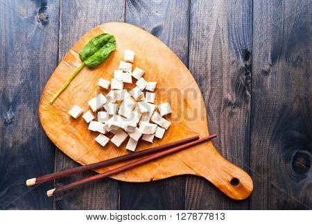 Cubes of raw tofu fresh spinach and chopsticks on rustic cutting board