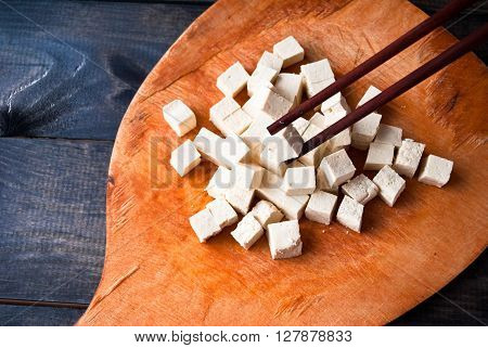 Cubes of raw tofu and two chopsticks with one of cubes