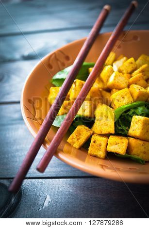 Salad from fried tofu with curry and fresh spinach in brown bowl with chopsticks. Vegetarian meal