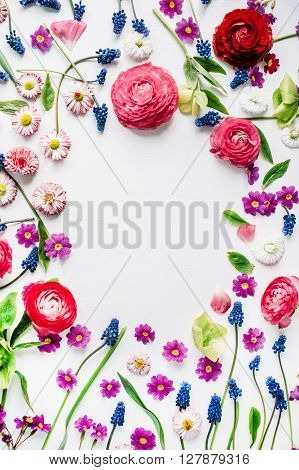 wreath frame with roses muscari chamomile ranunculus branches leaves petals and buds isolated on white background. flat lay overhead view