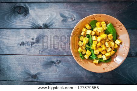 Salad from fried tofu with curry and green leaves of fresh spinach in brown bowl. Copy space