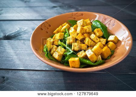 Salad from fried tofu with curry and green leaves of fresh spinach in ceramic bowl. Space for text