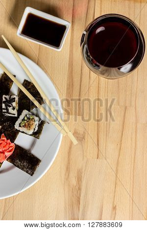 Sushi roll made dish. Sushi assorti on white plate with chopsticks soy souce glass of wine. Evening date closeup food photography