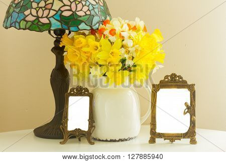 Fresh spring daffodils in white pot on table with empty art nuveau  frames