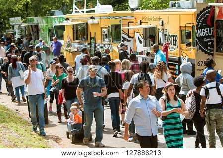 ATLANTA, GA - APRIL 2016:  A crowd of people survey their choices and buy meals from food trucks lined up at Grant Park at the Food-o-rama festival in Atlanta GA on April 16 2016 .