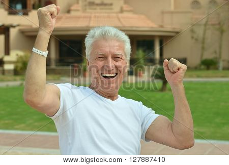 Portrait of a happy mature man with hands up