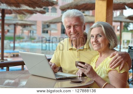 Mature couple sitting with laptop and coffee in hotel