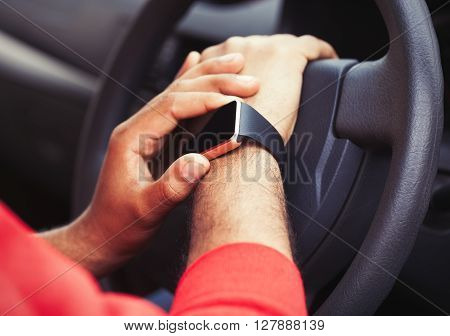 Hands Of African Man Using Smart Watch Sitting In A Car