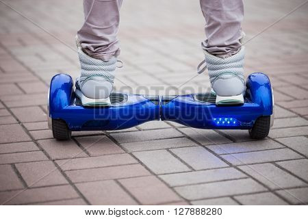 Person riding a modern blue electric mini segway or hover board scooterin outdoors. Popular new city transport that is easy and fun to ride and makes no air pollution to the atmosphere