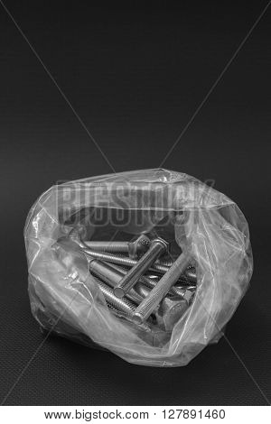 Bolts in a clear plastic bag on a black background to understand an industrialization concept