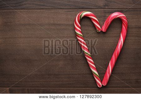 red sugar lollipops form heartshape on the wooden table