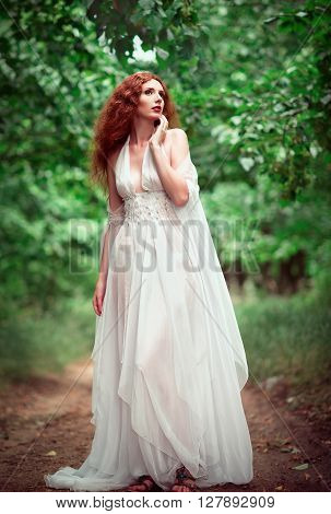 Beautiful ginger woman wearing white dress in the grove