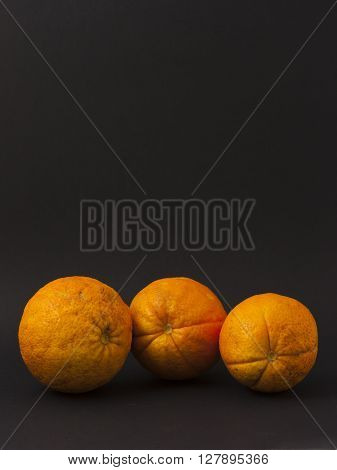 Three oranges on a black background to understand a concept for healthy eating