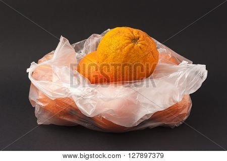 Oranges in a white envelope on a black background to understand a concept for healthy eating