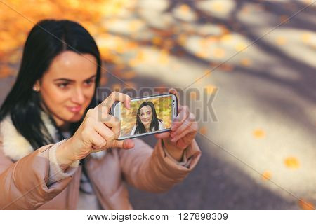 Happy Woman With Jacket Taking Selfie With Smartphone